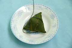 Dumplings in bamboo leaves. Traditional steamed Chinese rice dumplings, known as zongzi, wrapped in bamboo leaves, white studio background Royalty Free Stock Photos