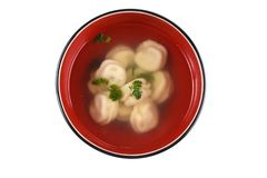 Dumplings in broth in a black and red cup on an isolated white background royalty free stock photo