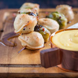 Dumplings and Brussels sprouts on skewers with cheese sauce Stock Photos