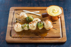 Dumplings and Brussels sprouts on skewers with cheese sauce. Skewers of fried dumplings and Brussels sprouts with cheese sauce Stock Images