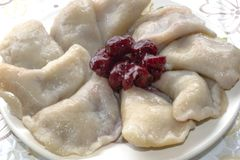 Dumplings with cherries lie on a plate royalty free stock photography