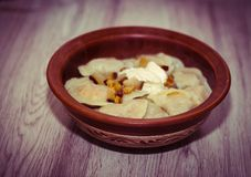 Dumplings in a clay plate on the wooden table. Dumplings, filled with mashed potato. Varenyky, vareniki, pyrohy - royalty free stock photos