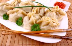 Dumplings filled on white plate with chopsticks and chilli sauce Stock Image