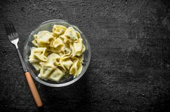 Dumplings in a glass bowl. On black rustic background royalty free stock photo