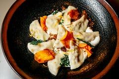 Dumplings, homemade ravioli in a plate on black background stock photos