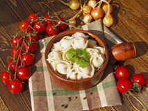 Dumplings with meat on a wooden table. With tomatoes and onions Stock Photography