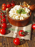 Dumplings with meat on a wooden table with tomatoes and onions Royalty Free Stock Photo