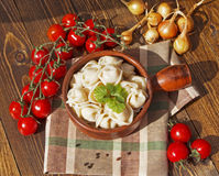 Dumplings with meat on a wooden table. With tomatoes and onions Royalty Free Stock Photography
