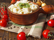 Dumplings with meat on a wooden table. With tomatoes and onions Royalty Free Stock Photo