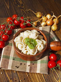 Dumplings with meat on a wooden table. With tomatoes and onions Stock Photo