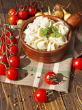 Dumplings with meat on a wooden table. With tomatoes and onions Royalty Free Stock Images