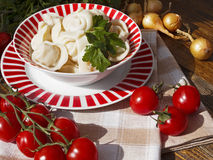 Dumplings with meat on a wooden table. With tomatoes and onions Royalty Free Stock Image