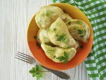 Dumplings parsley, green onions on a white wooden background fork. Dumplings parsley green onions on a white wooden background fork Stock Image