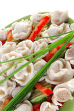 Dumplings with peppers on green Stock Photo