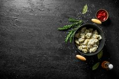 Dumplings in a pot of rosemary. On black rustic background stock photos