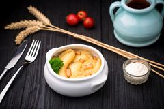 Dumplings with potatoes and cracknel on black wooden background Stock Images