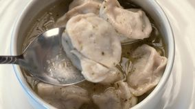 Dumplings in soup in white plate stock video footage
