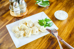 Dumplings with sour cream on a wooden table. Dumplings with sour cream on  wooden table Royalty Free Stock Images