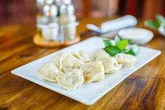 Dumplings with sour cream on a wooden table. Dumplings with sour cream on  wooden table Stock Photos