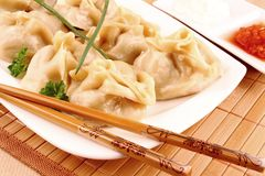 Dumplings on white plate with chopsticks and chilli sauce Stock Image