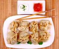 Dumplings on white plate with chopsticks and chilli sauce, view from top Stock Photography