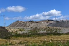 Terra-cone with belt conveyor system. Dumps of mined rock with spreader and working bulldozer, general view stock photo
