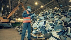 Dumpsite employee is observing a pile of broken electronic devices. Garbage, trash, waste recycling factory.