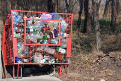 Dumpster for collection of plastic packaging. Full garbage container stands among trees Stock Photography
