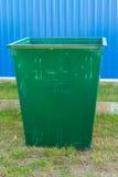 Dumpster die zich op het gras tegen de achtergrond van de omheining bevinden Royalty-vrije Stock Afbeeldingen