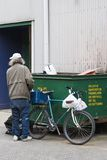 Dumpster Diver. A middle aged man, with grey hair and torn, baggy clothes, stands by his old bicycle and the dumpster where he has been searching for bottles Stock Image