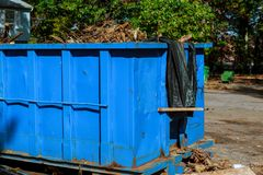 Dumpsters being full with garbage in a city. Royalty Free Stock Photo