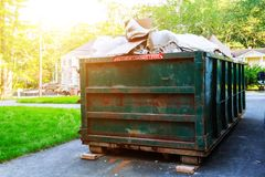 Dumpsters being full with garbage in a city. Stock Photos