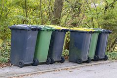 Dumpsters stand at the edge of the street.  stock photo