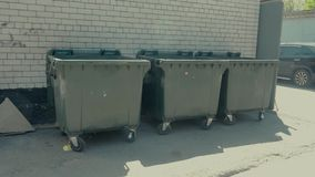 Dumpsters standing in front of a white brick wall stock footage