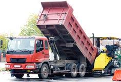 Dumptrack and asphalt spreading machine Stock Images