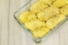 Dun gesneden aardappelplakken met kruiden in glasvorm Stock Afbeeldingen