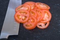 Dun gesneden plummy tomaten op zwarte scherpe raad Royalty-vrije Stock Afbeeldingen