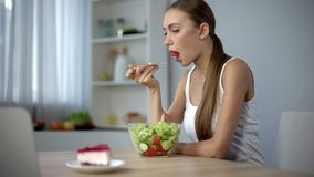 Dun wijfje die plantaardige salade eten maar over smakelijke cake, verleiding dromen stock fotografie