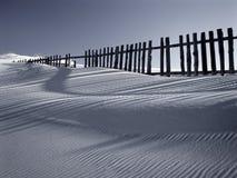 Duna de arena contra las cercas Foto de archivo libre de regalías