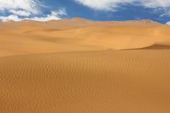 Duna de arena de oro y nubes blancas en un d?a soleado imagen de archivo libre de regalías