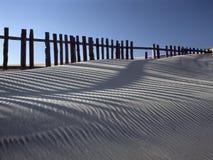 Duna di sabbia contro i recinti Fotografia Stock