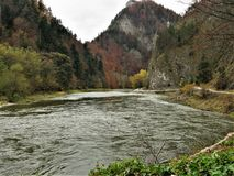 Dunajec River and Gorge between Poland and Slovakia in autumn. The Dunajec River flanked by trees with colourful autumn foliage and a path near the border of stock photos