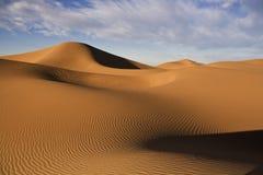 Dunas de arena del desierto con el cielo azul nublado Imagen de archivo libre de regalías