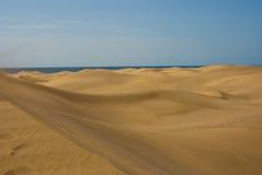 Dunas de arena del desierto con el mar en el horizont Foto de archivo libre de regalías