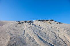Dunas de arena grises y el cielo azul Imagen de archivo libre de regalías