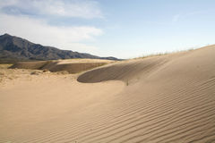 Dunas de arena que ondulan con un pico negro en el fondo Fotos de archivo libres de regalías