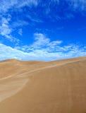 Dunas de arena quebradizas y cielo azul Imagen de archivo