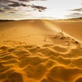 Dunas de arena y un hombre corriente en la arena caliente Foto de archivo libre de regalías
