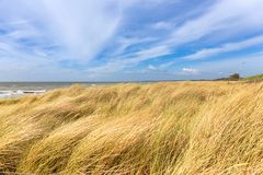 Dunas por el mar con vistas al agua y a un cielo azul Imagenes de archivo