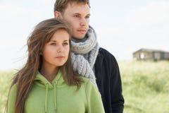 Dunas que hacen una pausa de los pares jovenes románticos con la playa Imagenes de archivo